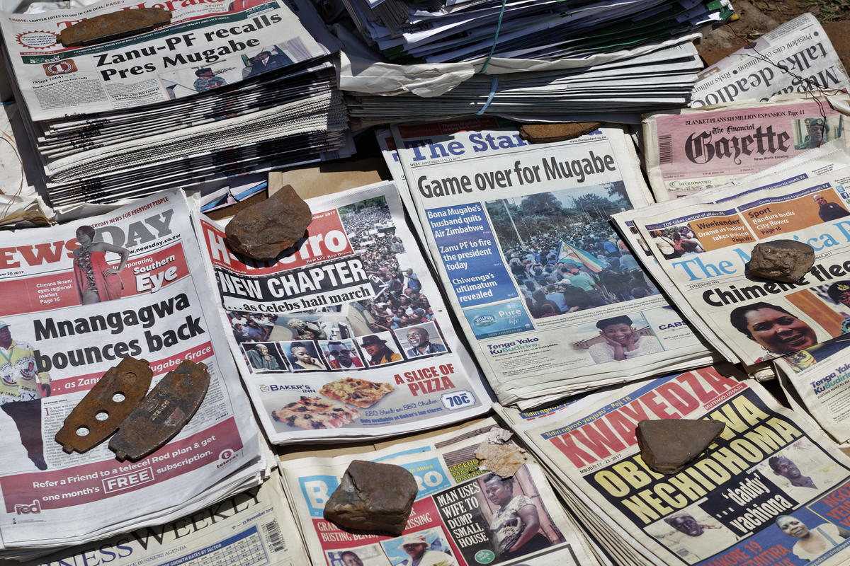 Newspapers are held down by rocks to stop them blowing away at a news stand in Harare, Zimbabwe Monday, Nov. 20, 2017. Longtime President Robert Mugabe ignored a midday deadline set by the ruling party to step down or face impeachment proceedings, while Zimbabweans stunned by his lack of resignation during a national address vowed more protests to make him leave. (AP Photo/Ben Curtis)