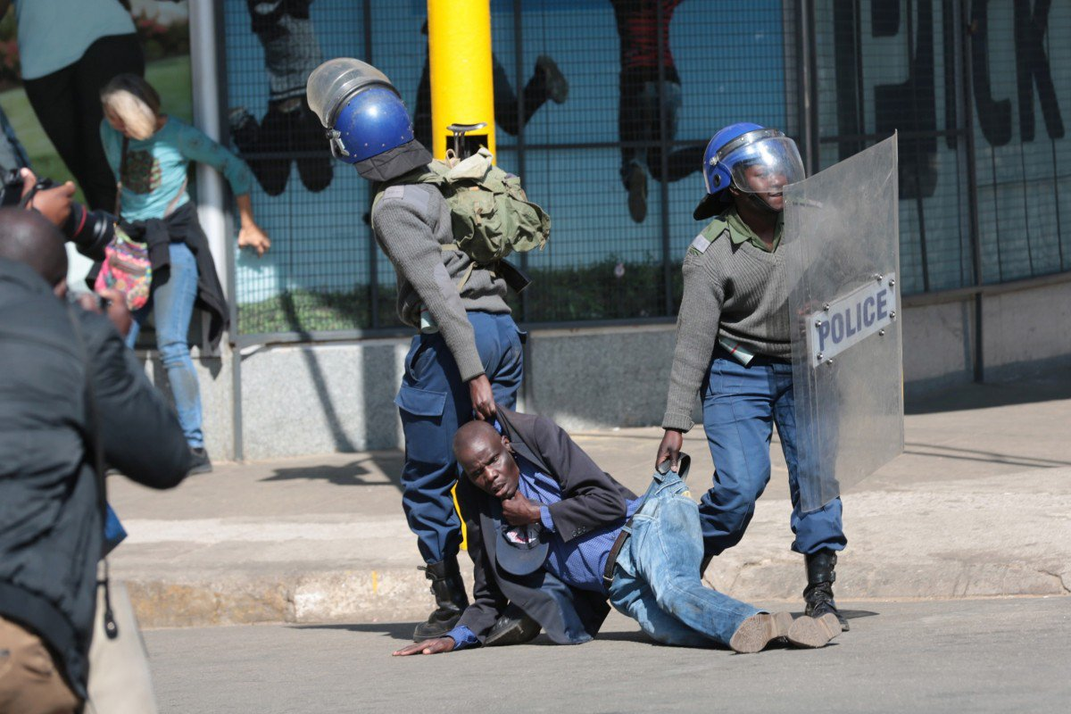 Zimbabwe Republic Police (ZRP) drag an injured protester during clashes in Harare on Friday. Photo- EPA-EFE